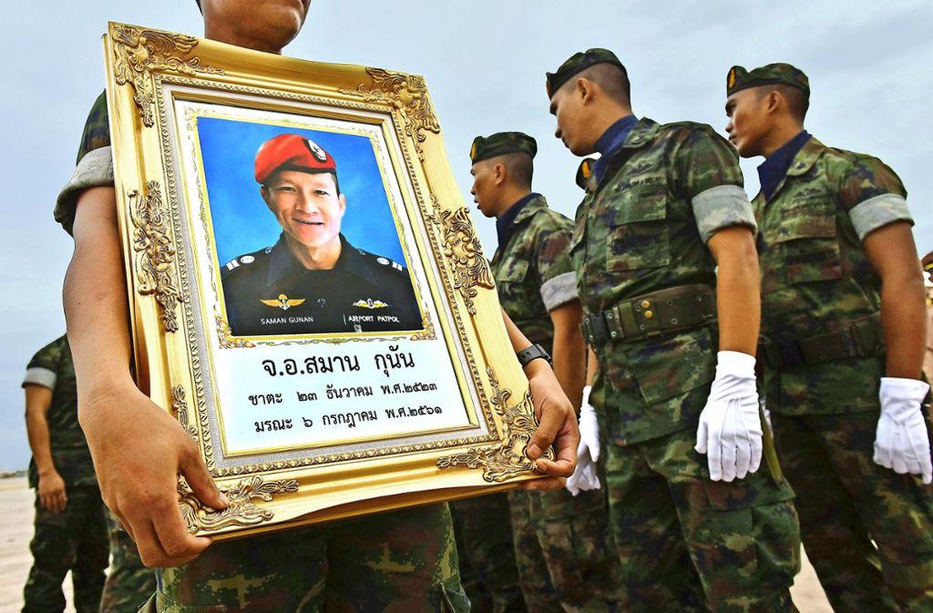 Ein thailändischer Marinetaucher hält das Porträt des verstorbenen Saman Gunan hoch. Foto: