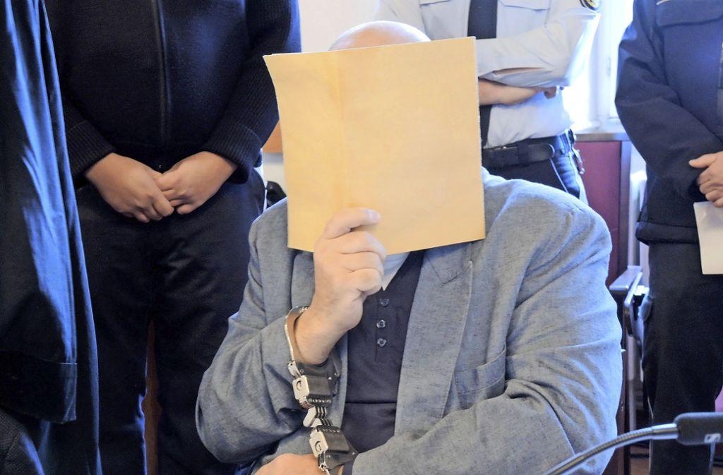 Ein Angeklagter verdeckte im Ellwanger Mordprozess sein Gesicht. Der 55-Jährige Vater soll laut Urteil nie wieder auf freien Fuß kommen. Foto: dpa/Thomas Burmeister