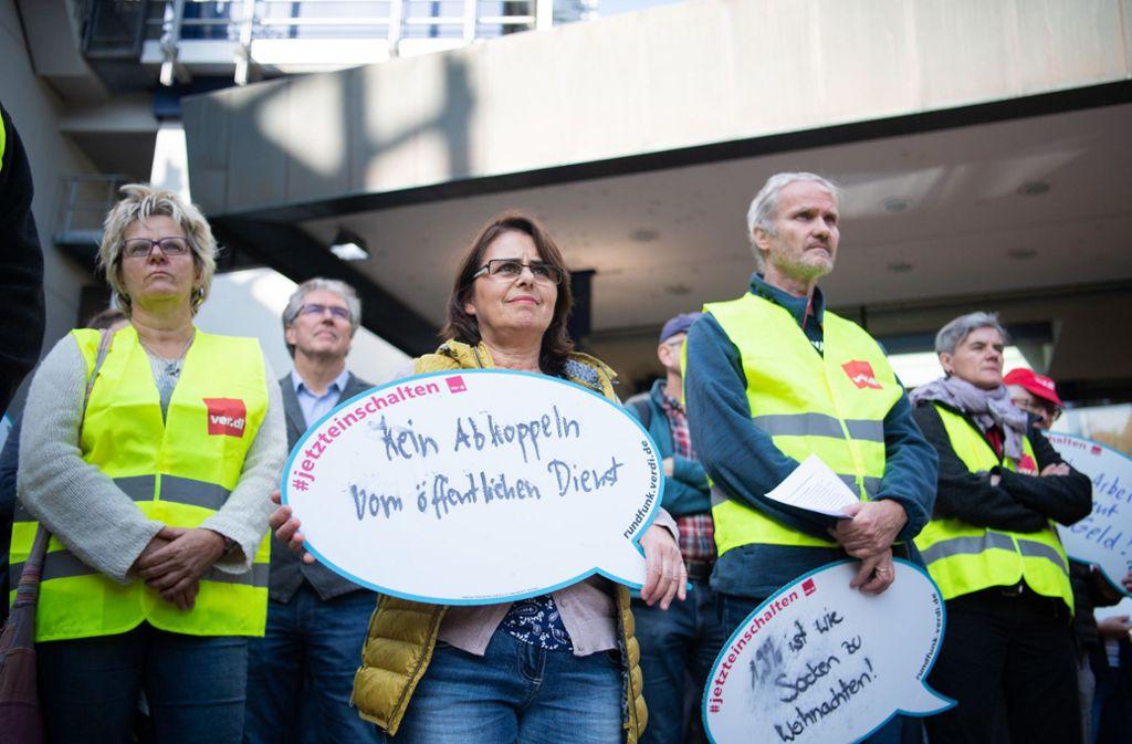 Mitarbeiter stehen mit Schildern bei der Kundgebung vor dem SWR-Gebäude. Foto: dpa/Tom Weller