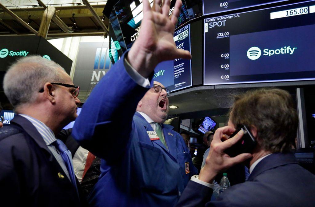 Peter Giacchi (Mitte), Market-Maker an der New Yorker Börse, steht vor Bildschirmen, und erklärt den Handel mit Aktien des Streaming-Musikdienstes Spotify für eröffnet. Foto: AP