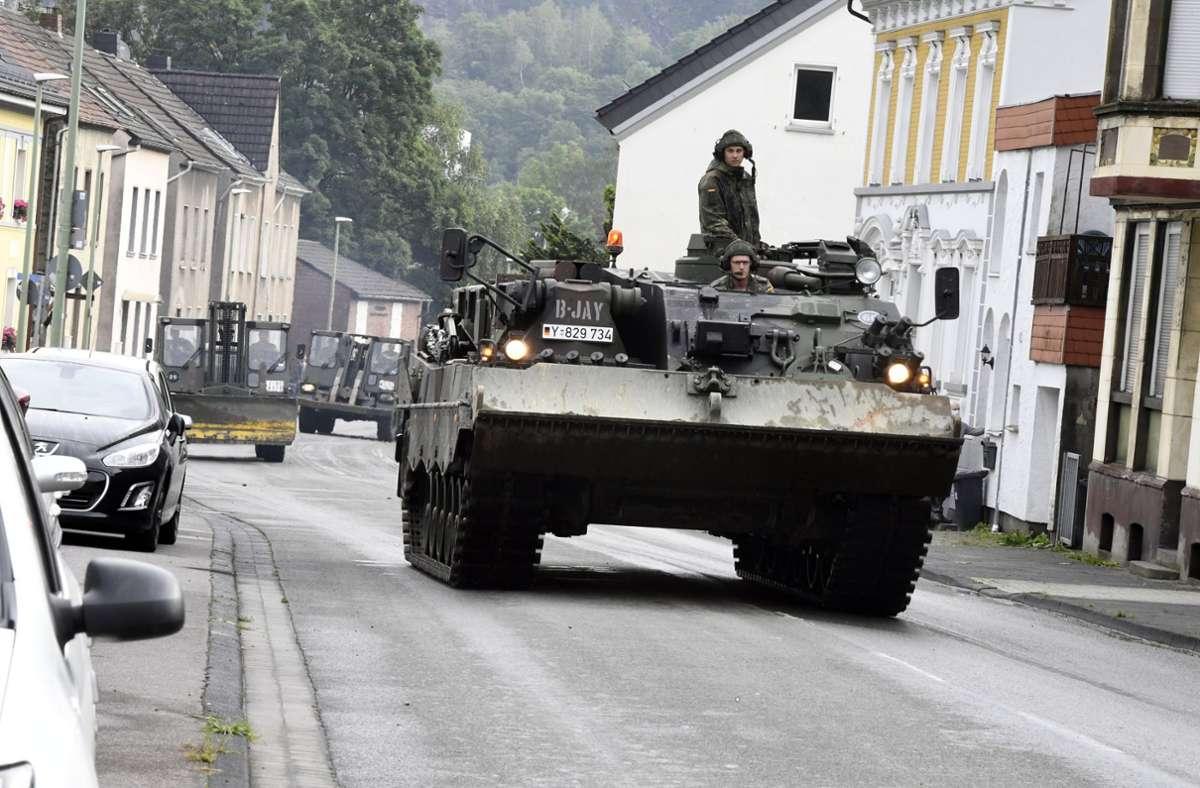 Mit einem Bergepanzer und schwerem Räumgerät rückt die Bundeswehr an, um die Schäden in Hagen, in Nordrhein-Westfalen, zu beseitigen. Foto: dpa/Roberto Pfeil