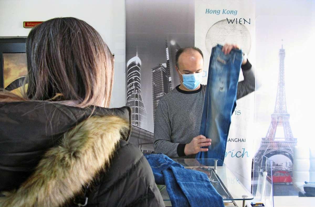 Die Kundin freut sich, in dem von ihr geschätzten Laden einkaufen zu können.  Der Inhaber Zeljko Vukmirovic faltet die neuen Hosen hinter der Hygieneschutzscheibe zusammen. Foto: Eva Schäfer