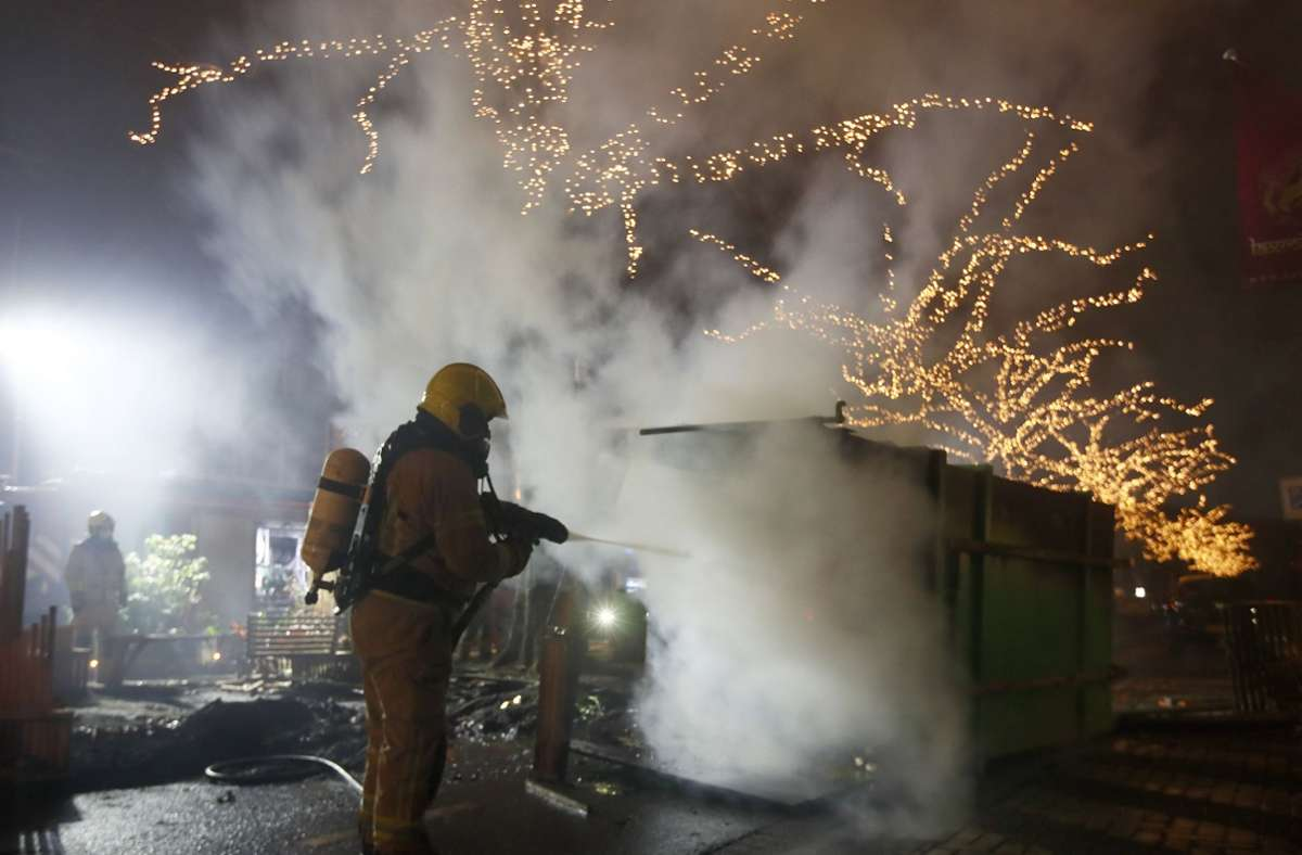 Ein Feuerwehrmann löscht in Rotterdam einen Container, der bei Protesten gegen eine landesweite Ausgangssperre in Brand gesetzt wurde. Foto: dpa/Peter Dejong