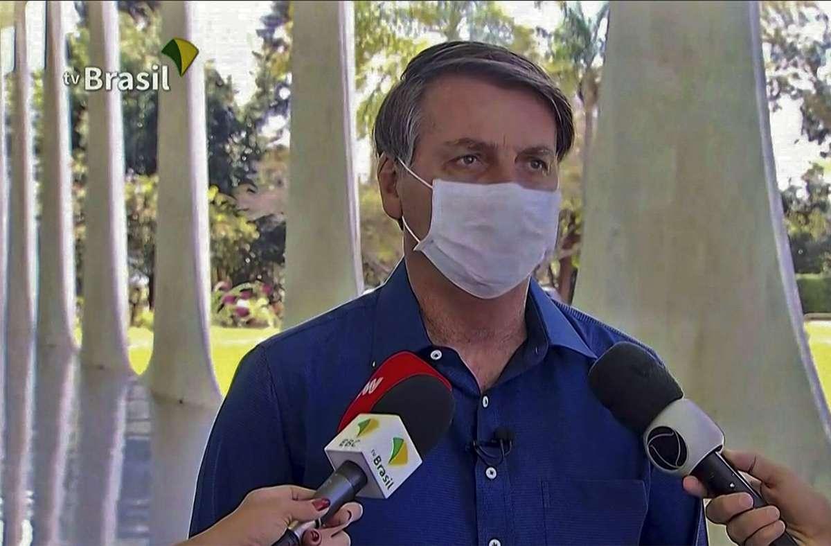 Der brasilianische Präsident Jair Bolsonaro zieht sich vor laufender Kamera den Mundschutz ab – kurz nachdem er erstmals öffentlich verkündet hat, dass er mit dem Coronavirus infiziert worden ist Foto: AFP