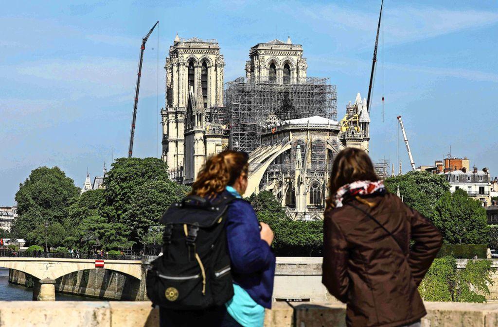 Zwei Frauen betrachten in Paris die bei einem Brand schwer geschädigte Kathedrale von Notre-Dame. Foto: AFP