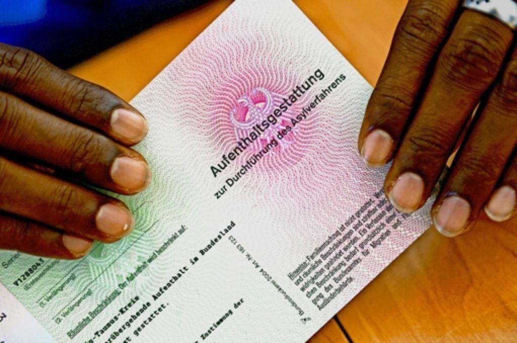 """Die Anträge von Asylbewerbern sollen zügig bearbeitet werden, fordern fünf Bürgermeister in einem Brief. Ein Flüchtling aus Somalia zeigt seine """"Aufenthaltsgestattung"""". Foto: dpa"""