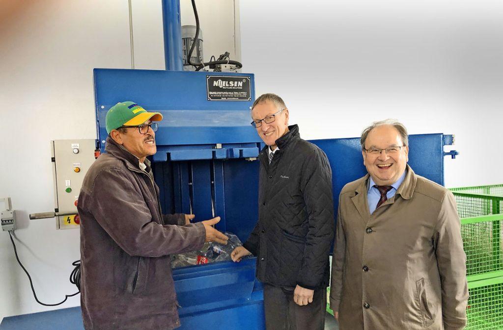 Ein Mitarbeiter des neuen Wertstoffhofs zeigt dem Landrat Roland Bernhard (Mitte) und dem Böblinger Abfallchef Wolfgang Bagin, wie die Kunststoffpresse funktioniert Foto: StZ