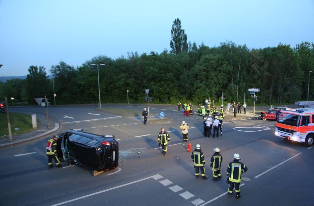 Rettungskräfte untersuchen auf einer Kreuzung in Hagen ein nach einem Unfall zerstörtes Fahrzeug. Bei einem illegalen Autorennen sind fünf Wageninsassen schwer verletzt worden, darunter ein kleiner Junge. Foto: dpa