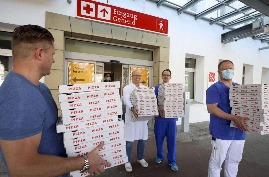 Klinik-Mitarbeiter nehmen die Pizzen in Empfang. Foto: factum/Simon Granville
