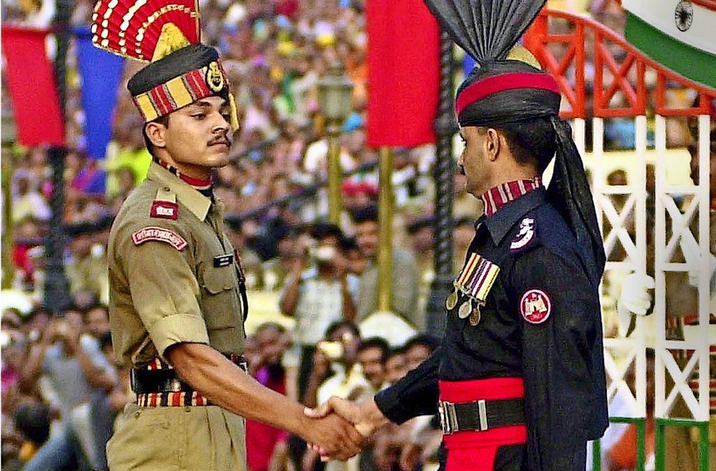 Ein pakistanischer (rechts) und ein indischer Grenzbeamter. Foto: EPA