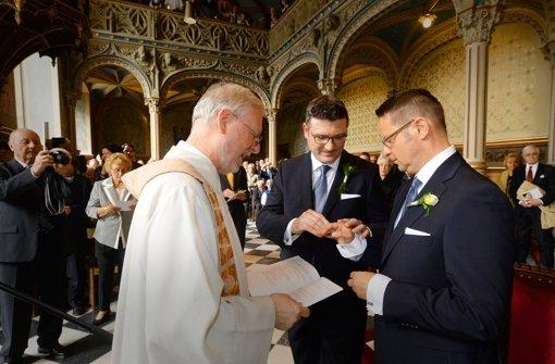 Stefan Kaufmann (Mitte) und Rolf Pfander tauschen Ringe in der Schlosskirche. Foto: dpa