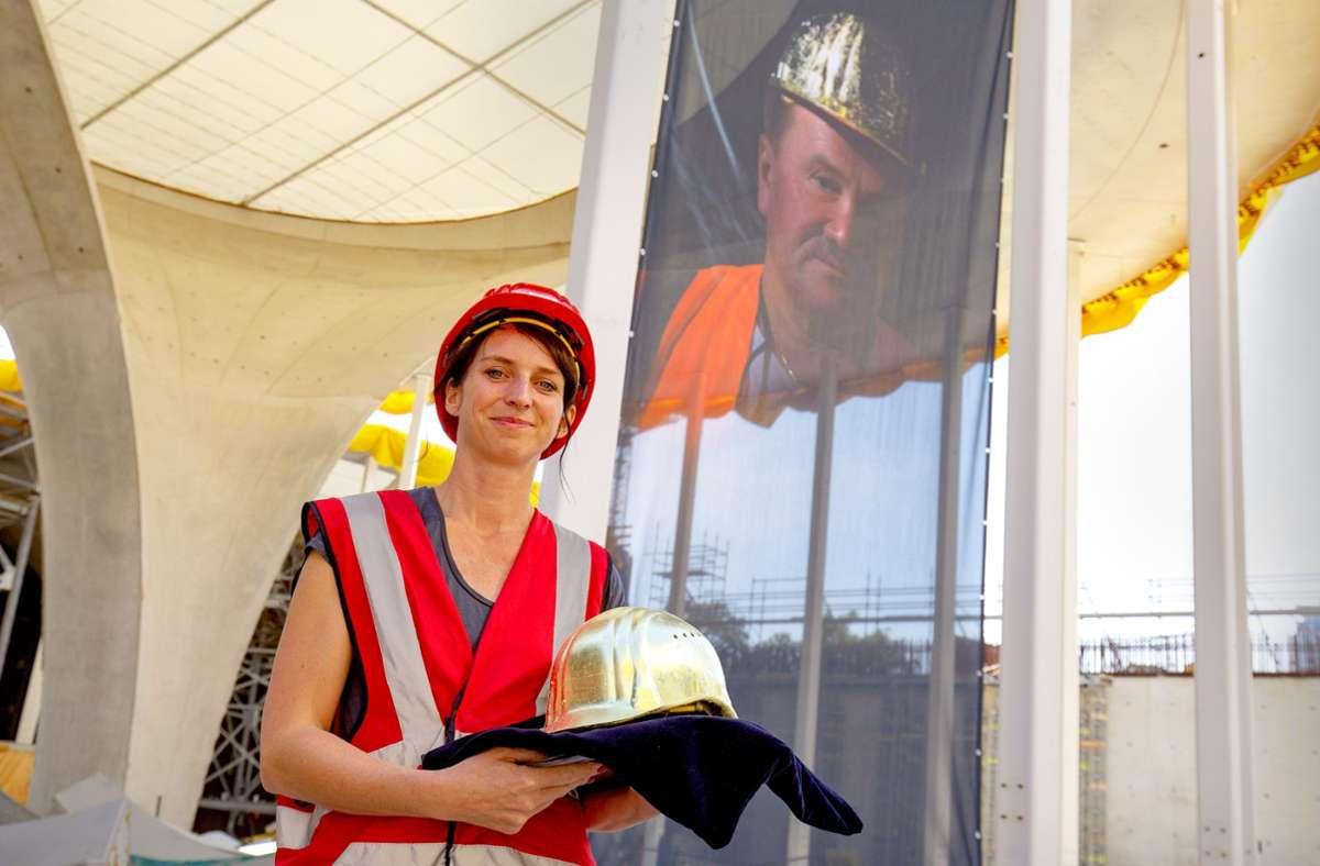 """Die Künstlerin Nina Nielebock vor ihrer Fotografie """"Der Mann mit dem Goldhelm"""" an  einer Kelchstütze des Bahnhofs. Foto: Lichtgut/Leif Piechowski"""