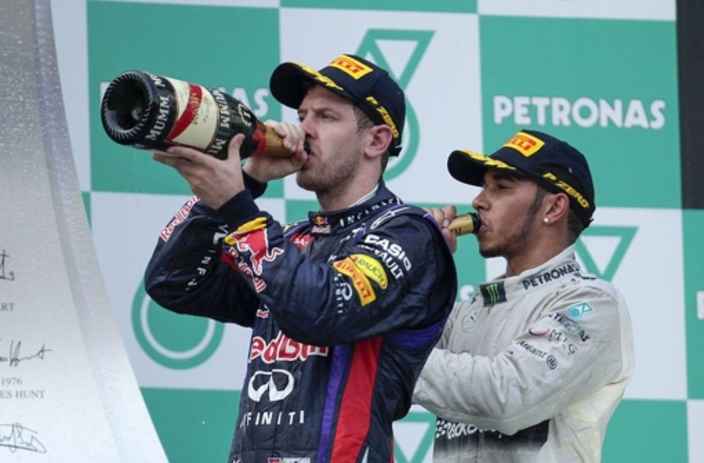 Sebastian Vettel (links) und Lewis Hamilton lassen es sich schmecken. Foto: dpa