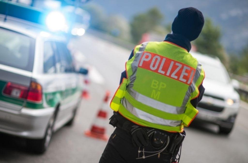 Ein Polizeibeamter macht Stichproben an der Anschlussstelle Bad Reichenhall der Autobahn A8 von Salzburg nach München (Bayern) bei Fahrzeuge, die aus Österreich kommen. (Archivfoto) Foto: dpa