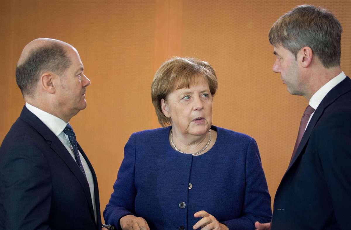 Jan Hecker (rechts) im Gespräch mit Bundeskanzlerin Angela Merkel und Olaf Scholz. Foto: dpa/Kay Nietfeld