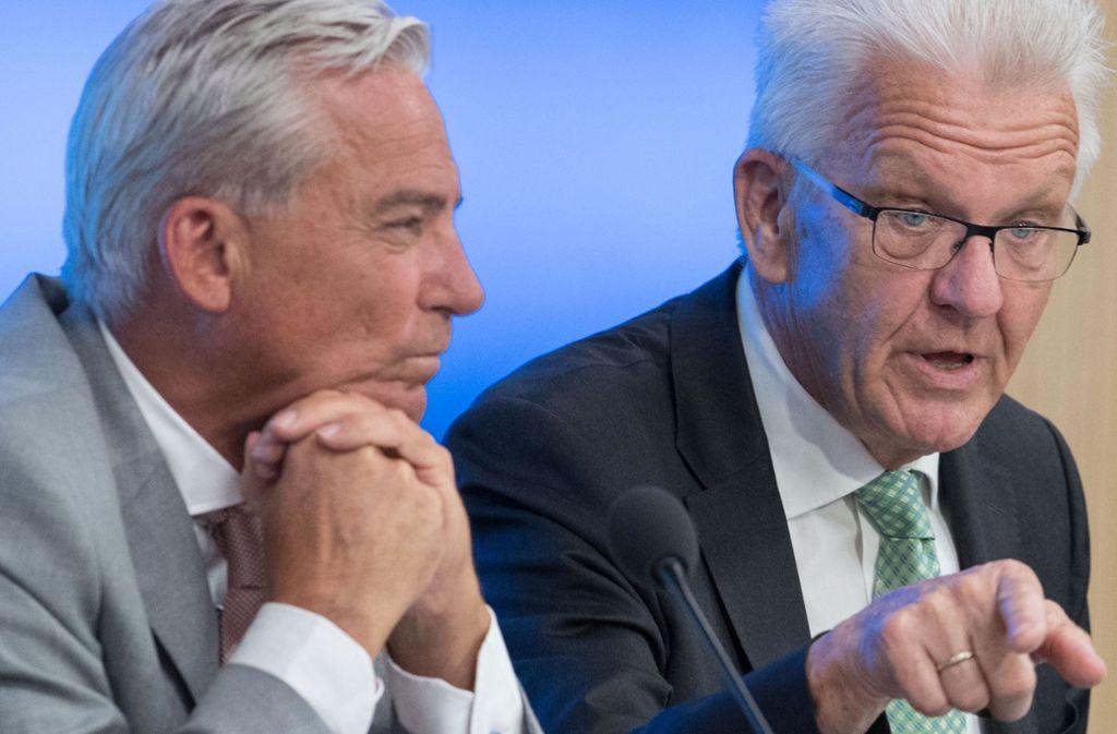 """Dieser Blick sagt mehr als viele Worte: Ministerpräsident Kretschmann, flankiert von Innenminister Strobl, wirft der Bundesregierung einen """"Frontalangriff"""" auf die Länder vor. Foto: dpa"""