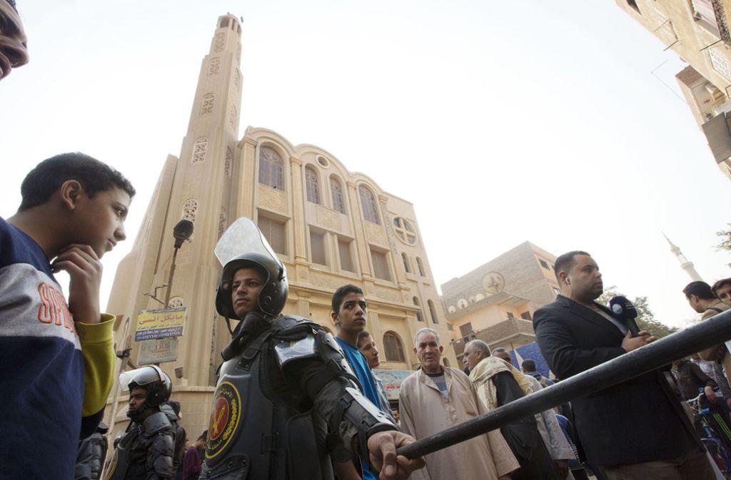 Ägyptische Polizisten sichern das Gelände vor einer Kirche nahe Kairo. Foto: AP