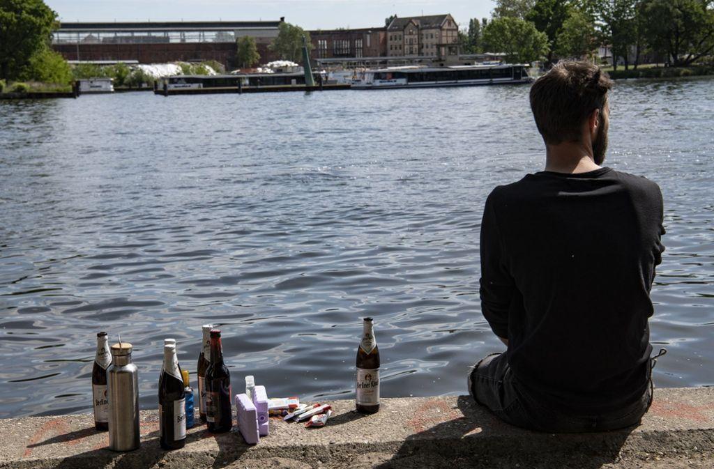 Ein Mann sitzt am Vatertag am Ufer der Spree in Berlin-Treptow Foto: dpa/Paul Zinken