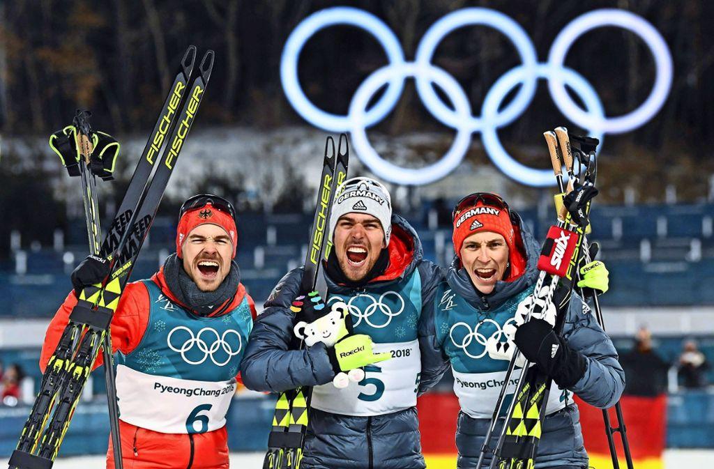 Fabian Rießle, Johannes Rydzek und Eric Frenzel (v.l.) feiern ihren historischen Erfolg bei Olympia 2018. Foto: AFP