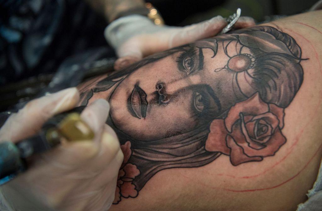 Eine Frau lässt sich auf der Internationalen Tattoo-Convention in Frankfurt am Main ein weibliches Gesicht in den Oberschenkel stechen. Foto: Boris Roessle