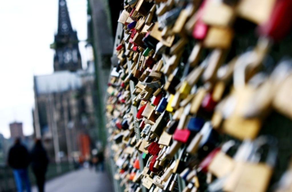 Die Hohenzollernbrücke in Köln ist vollgehängt mit Schlössern – als Symbol von Liebenden, die sich dort die ewige Treue versprechen. Foto: dpa