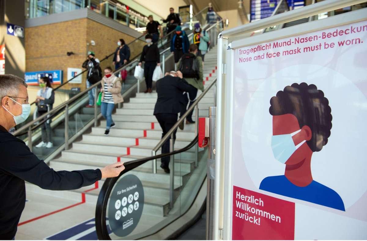 Brandenburg, Potsdam: Passanten mit Mundschutz gehen im Hauptbahnhof an einem Schild der Bahnhofs-Passagen mit der Aufschrift «Herzlich willkommen zurück! Tragepflicht Mund-Nasen-Bedeckung.» vorbei. Foto: picture alliance/dpa