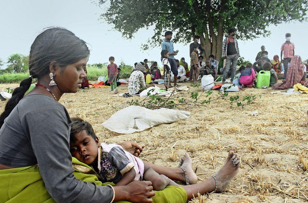 Die Wanderarbeiterin Budhu Baimit mit ihrem Sohn  im Dorf Bandha im Morena Distrikt in Madhya Pradesh zusammen mit anderen Wanderarbeitern. Foto:
