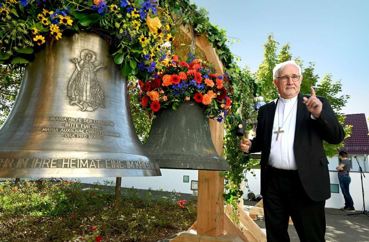 Bischof Gebhard Fürst neben den beiden Glocken, die bislang in der Kirche Maria Hilfe der Christen in Aichtal-Grötzingen hingen. Foto: dpa/Bernd Weißbrod