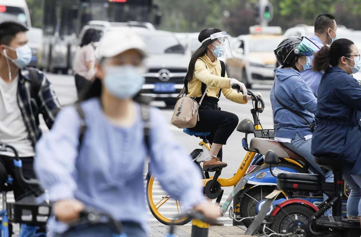 Menschen in Wuhan tragen Mund-Nasenbedeckungen, während sie zur morgendlichen Rush Hour im Stadtverkehr. (Archivbild) Foto: dpa/kyodo