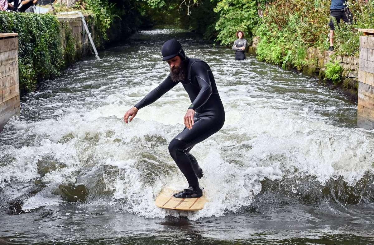 """Surfer Jonas Buchholz steht auf einem Surfbrett in der Anlage """"Blackforestwave"""", die am Freitag offiziell eingeweiht wurde. Foto: dpa/Uli Deck"""