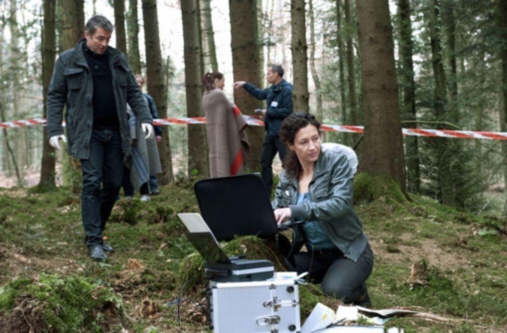 Die Ermittlungen führen die beiden Beamten in den Wald. Foto: SRF/Daniel Winkler