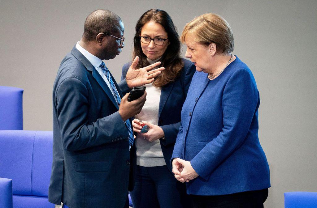 Merkel (r.) redet mit  den Abgeordneten Diaby (l.) und Fahimi (m.) Foto: dpa/Kay Nietfeld