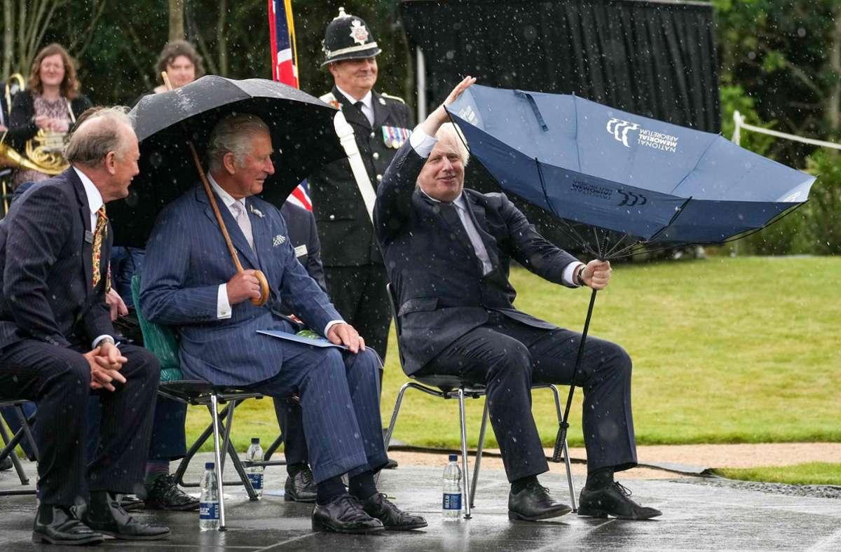 """Der Regenschirm wollte nicht so, wie Boris Johnson wollte – und Prinz Charles (Mitte) war """"amused"""". Foto: AFP/CHRISTOPHER FURLONG"""