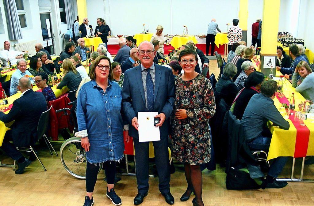 Bezirksbeirätin Birgit Närger (links), Dieter Strohmayer (mit Ehrenmedaille)  und Bezirksvorsteherin Mina Smakaj posieren  vor den Ehrenamtlichen. Foto: Susanne Müller-Baji