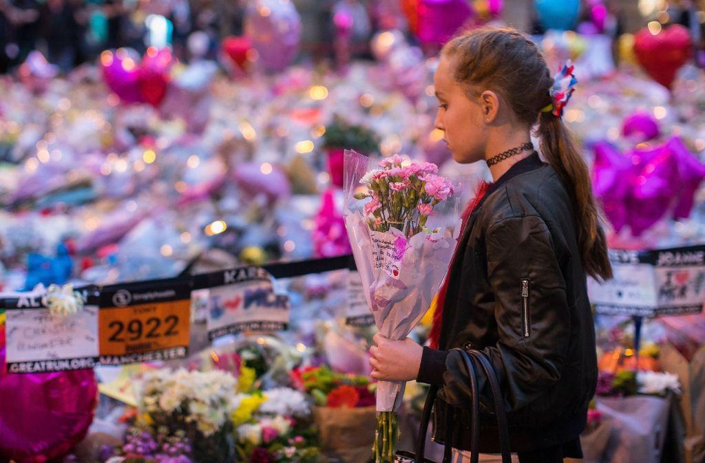 Ein Mädchen legt in Manchester Blumen für die Opfer des Anschlags nieder. Foto: London News Pictures via ZUMA