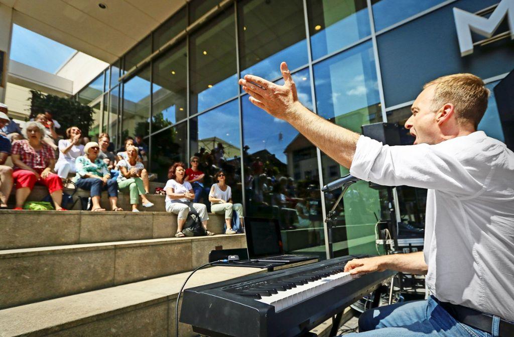 """Der Füenf-Star Patrick """"Memphis""""  Bopp singt mit Passanten vor dem Marstall-Center """"Biene Maja"""". Auf dem Marktplatz gab es zuvor mit ihm einen Peter-Maffay-Block. Foto: factum/Granville"""