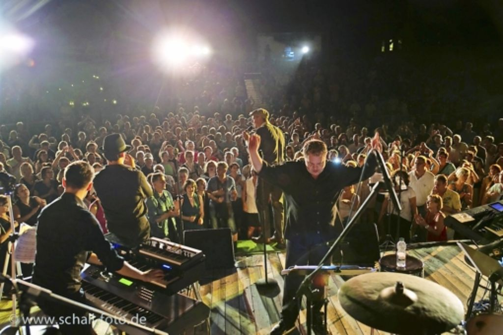 Alexander Eissele dirigiert die Big Band, dahinter rockt Max Mutzke das Publikum im Adelberger Klosterhof. Foto: Jürgen Schall