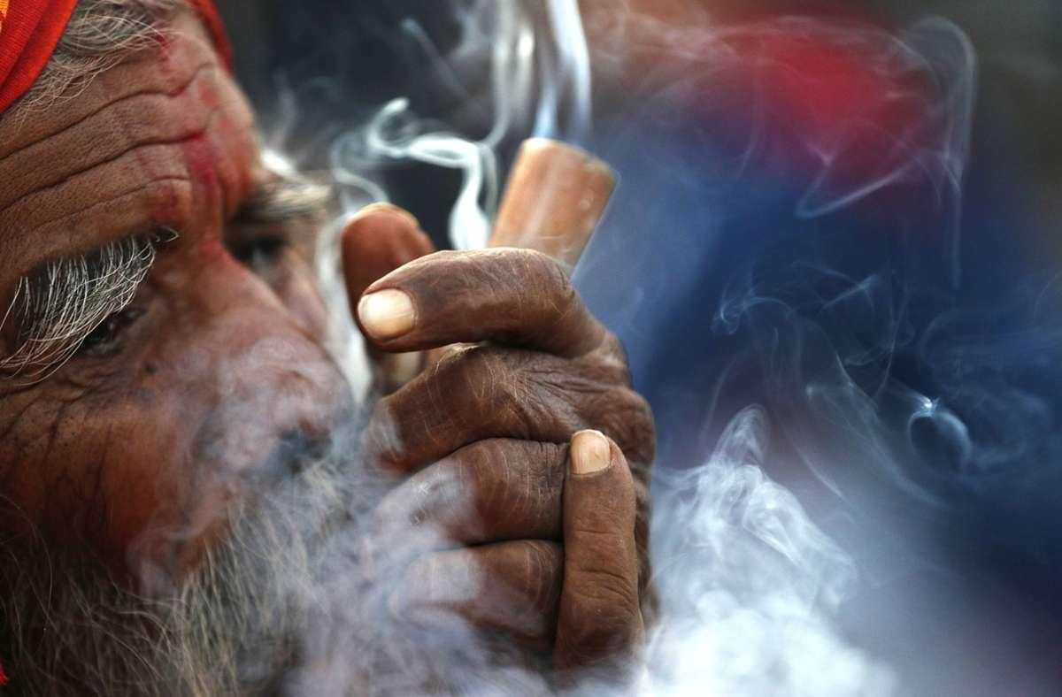 Wo ist Cannabis legal? Ein Hindu raucht im Hof des Pashupatinath-Tempels während des Shivratri-Festes in Nepal Cannabis. Foto: dpa/Niranjan Shrestha
