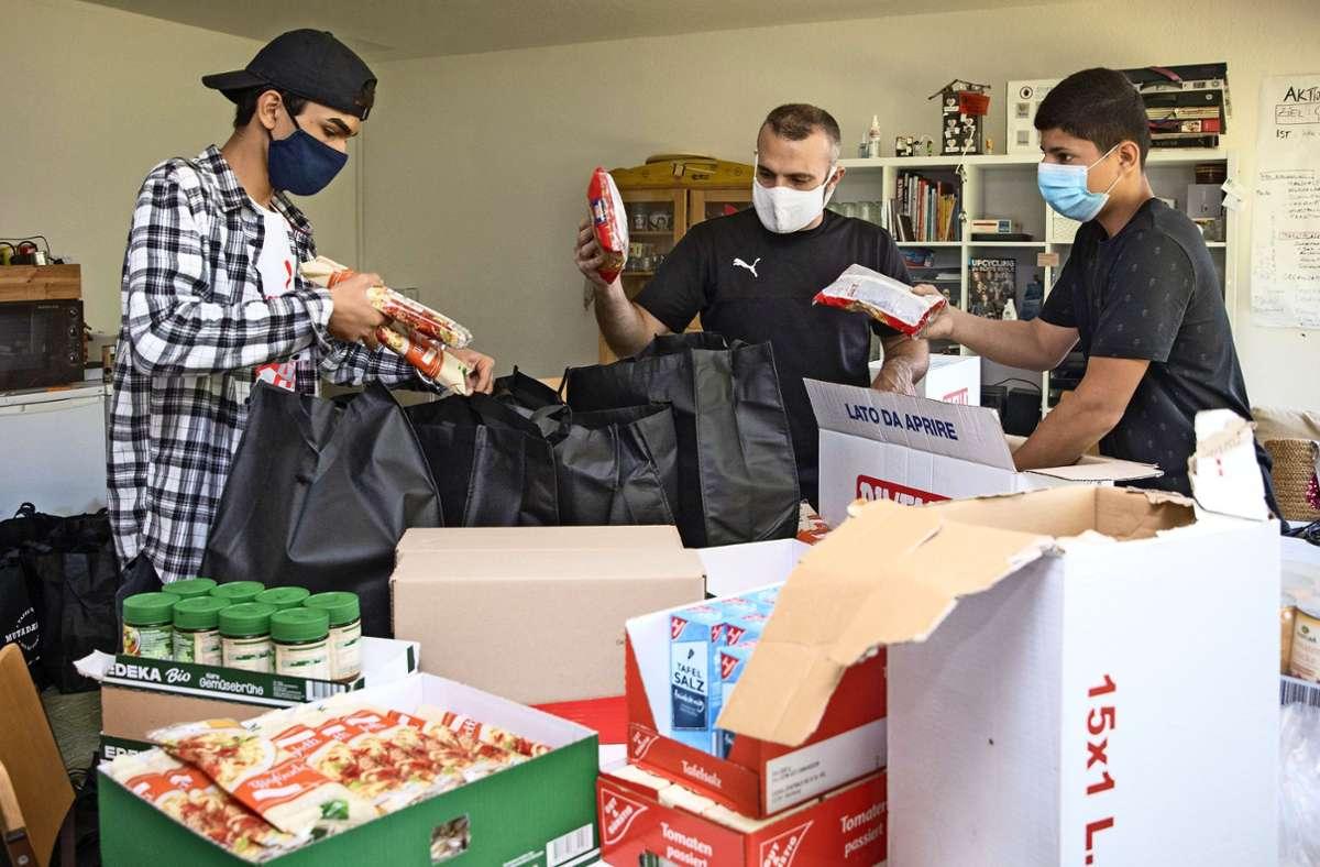 Mansour Niazi, Obeda Bazzi und Mohamad Sheikh (von links) packen vor ihrer Lieferrunde die Lebensmittel in Taschen. Foto: Frank Eppler