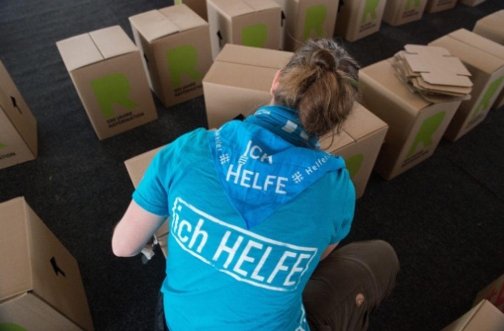 """Eine Freiwillige baut auf dem Kirchentag in Stuttgart Papphocker zusammen. Die Helfer bekommen Verpflegung und Unterkunft – und """"das gute Gefühl, ein bedeutendes Großereignis gemeinsam zu stemmen"""". Das motiviert mehr, als es Geld tun könnte, wie man in diesem Facebook-Video sieht. Foto: dpa"""