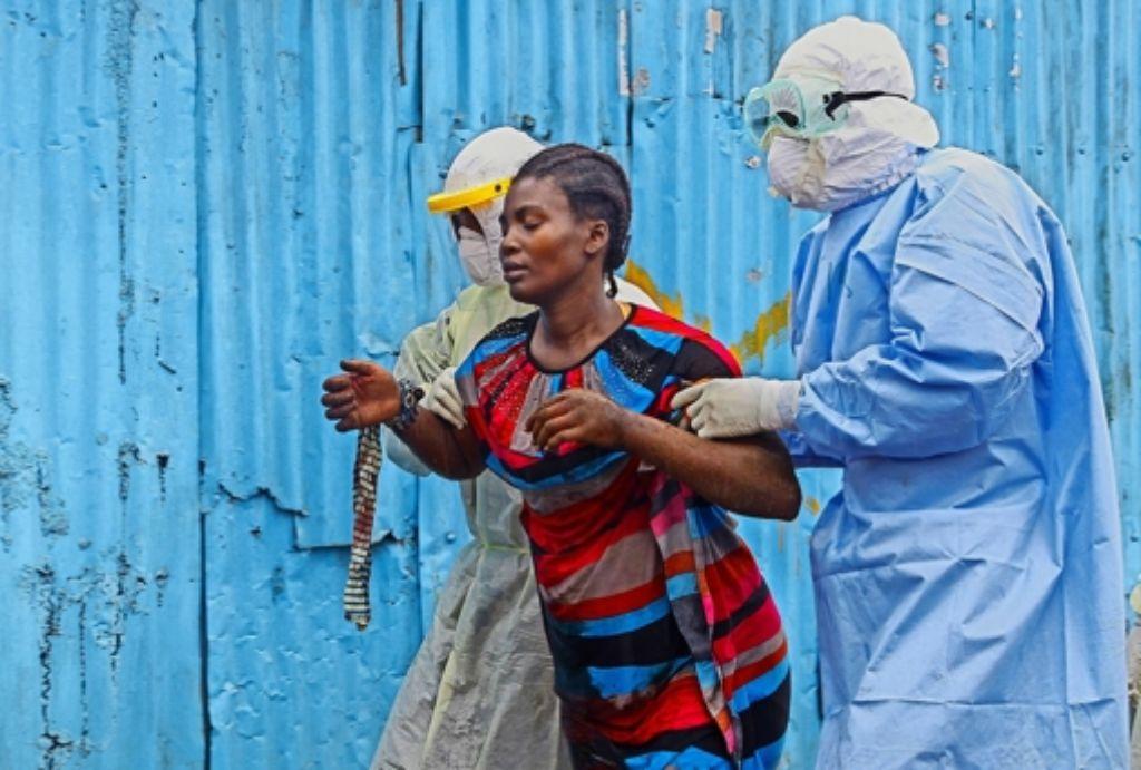Eine Frau mit Ebola-Symptomen wird ins Krankenhaus gebracht. Sie hat noch Glück – viele Patienten werden vor den Toren abgewiesen. Foto: dpa