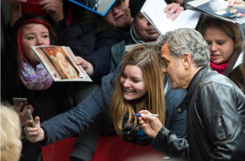 """Das mit dem Unterschreiben wird schwierig, aber ein Selfie mit George Clooney ist ja auch nicht schlecht. Bilder vom Trubel vor der Berlinale-Premiere von Clooneys Film """"Hail Caesar"""" zeigt die folgende Fotostrecke. Foto: dpa"""