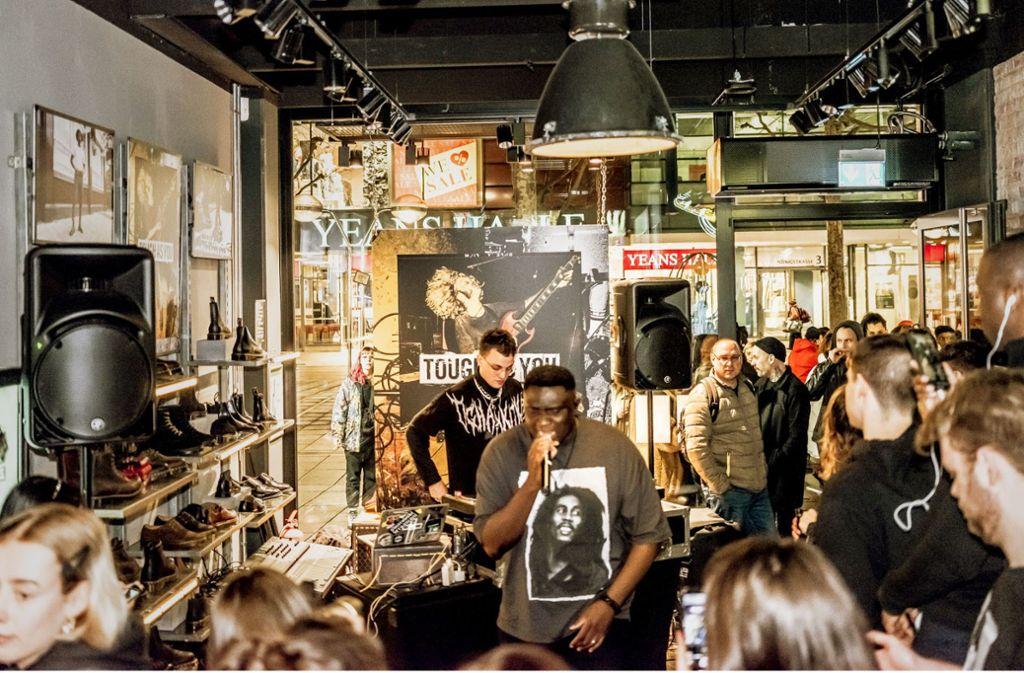 Der Sänger  Kwadi mit dem Cro-DJ Psaiko Dino (dahinter) bei der Eröffnungsparty von Doc  Martens auf der Königstraße. Foto: Andreas Engelhard