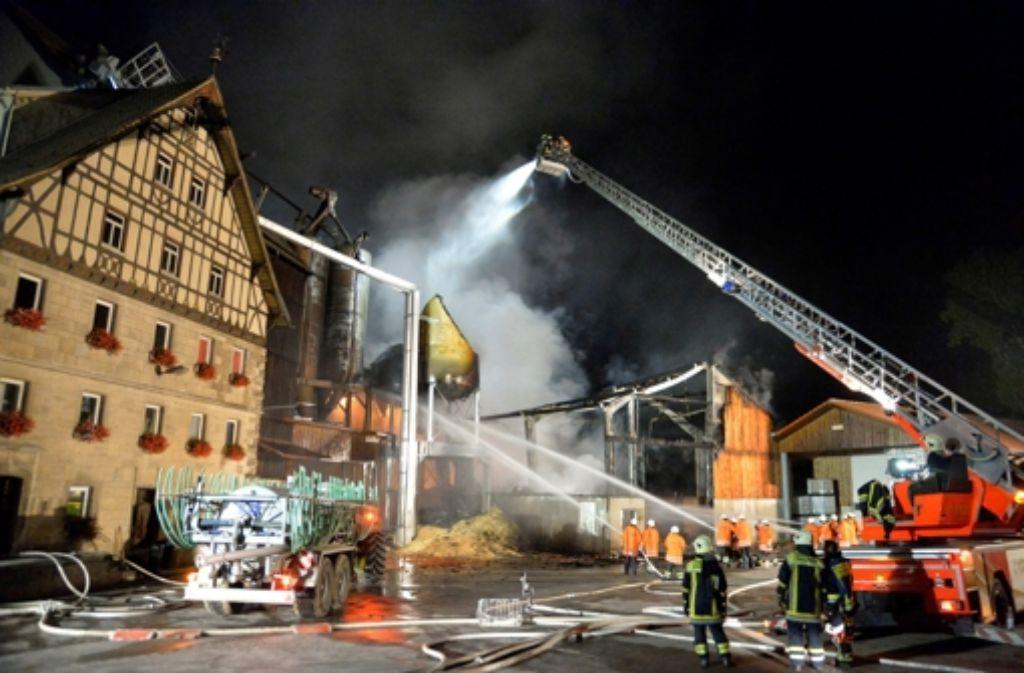 Einsatzkräfte der Feuerwehr löschen am 23.08.2015 in Kirchberg an der Jagst einen brennenden Mühlenbetrieb. Foto: dpa