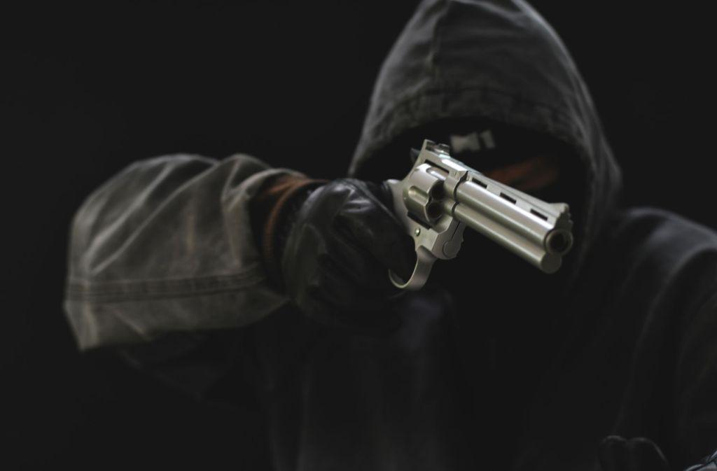 Einer der Täter bedrohte den Angestellten mit einer silbernen Pistole. (Symbolbild) Foto: Shutterstock/Lovely Bird