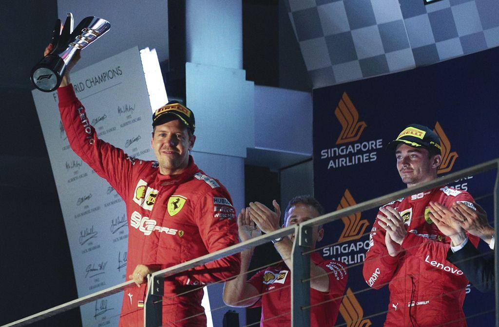 Sebastian Vettel (li.) ist in Singapur im Glück, Charles Leclerc applaudiert fair – doch innerlich kochte es in  dem Monegassen. Foto: AP/Lim Yong Teck