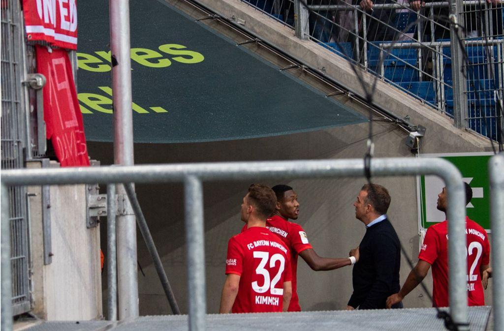 Bayern-Spieler und Trainer Hansi Flick reden auf die Fans ein. Foto: dpa/Tom Weller