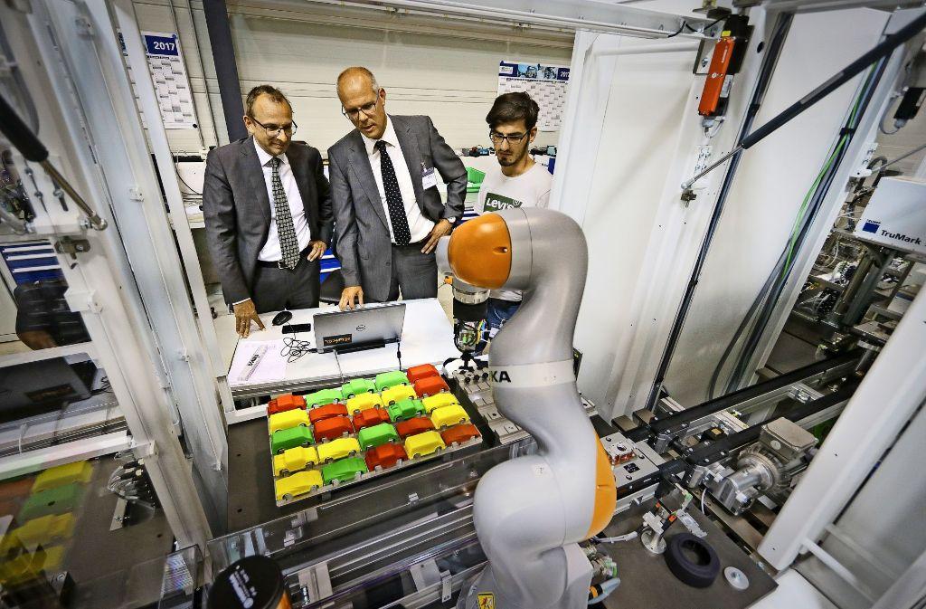 Der Teamtechnik-Chef Stefan Roßkopf (links) und der Schulleiter Stefan Ranzinger begutachten die Lernfabrik. Das Herzstück ist ein Montageroboter. Foto: factum/Granville