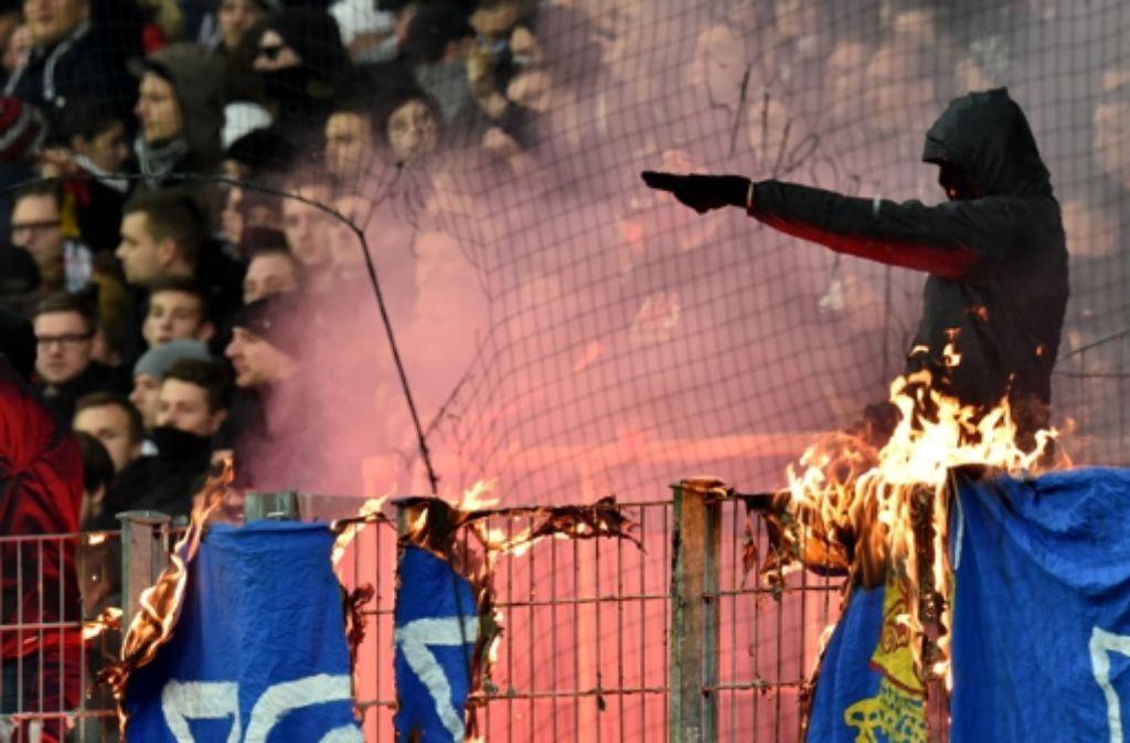Die Frankfurter Fans brennen Darmstädter Fahnen und Schals ab. Foto: dpa