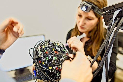 Die Arbeitswissenschaftler lassen Freiwillige am Computer Aufgaben erledigen und messen dabei die Hirnströme (links). Die Software funktioniert absichtlich ab und zu nicht und ärgert den Probanden. Welche Gefühle er bei der Arbeit hat, versuchen die Forscher dem Vergleich der Hirnstrombilder bei Erfolg und Misserfolg zu entnehmen (rechts). Foto: Parsyak/IAO